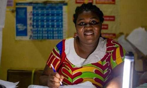 Nurse at Aid Station enjoys light from Sunjack and Light Stick units in Obosono Village Ghana